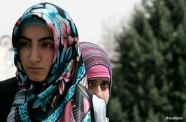 FILE - Two female protesters attend a demonstration against the ban on wearing headscarves at a rally in Ankara.