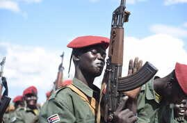 A South Sudanese government army soldier slaps his gun at Jebel Makor, 45 minutes outside South Sudan's capital Juba, April 14, 2016. The soldiers were brought here as part of a process to reduce the number of troops in the city before the arrival of