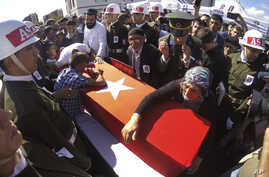 Fehime Aydemir (R), the mother of Turkish officer Metin Aydemir, cries over his flag-draped coffin during funeral services in his hometown of Erzurum, eastern Turkey, Aug. 19, 2015. Aydemir was one of the three officers killed Tuesday in an operation