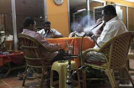 Customers smoke waterpipes at a Shisha cafe in Khartoum April 28, 2013