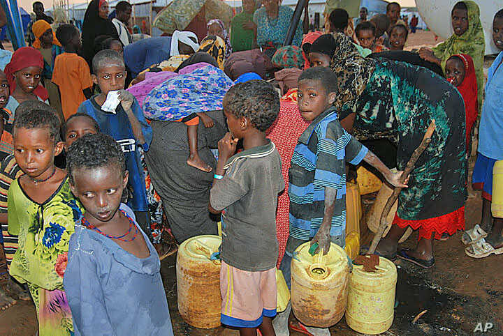Women and children crowd around the public water taps at the Dollo Ado refugee transit facility in Ethiopia, October 26, 2011. (VOA - P. Heinlein)
