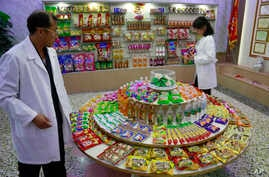 In this Oct. 22, 2018, photo, Kwon Yong Chol, left, the chief engineer at the Songdowon General Foodstuffs Factory, shows samples of products at his facility in Wonsan, North Korea.