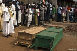 People pray next to caskets containing bodies of two men killed by sectarian violence in Muslim neighborhood of Bangui, March 23, 2014.