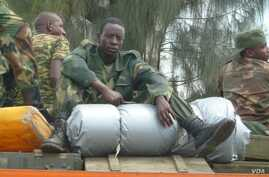 An M23 soldier rests his on boxes of ammunition as the group withdraws from the city of Goma, DRC, December 1, 2012 (photo - VOA/G. Joselow).