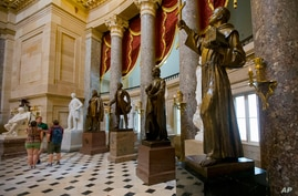 A statue of missionary Junipero Serra, right, is seen in Statuary Hall, also known as the Old Hall of the House, on Capitol Hill in Washington, July 2, 2015.