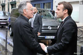 French President Emmanuel Macron (R) is welcomed by the archbishop of Marseille and president of the Bishops' Conference of France (CEF) Georges Pontier, upon his arrival at a meeting of the Bishops' Conference of France (CEF) at College des Bernardi