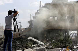 A journalist films the wreckage of a building described as part of the Scientific Studies and Research Centre (SSRC) compound in the Barzeh district, north of Damascus, during a press tour organised by the Syrian information ministry, on April 14, 20...