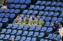 Soldiers sit in the empty seats held by the IOC as they watch the women's gymnastics qualification in the North Greenwich Arena during the London 2012 Olympic Games July 29, 2012.