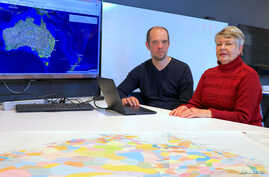 A supplied image shows University of Newcastle research academic, Professor Lyndall Ryan, and researcher Bill Pascoe sitting in front of a screen July 18, 2018, displaying a map detailing the number of Aboriginal and Torres Strait Islander massacres