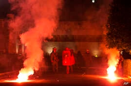 Covered with red paint Riot police officers stand among flares thrown by protesters during a rally outside the Greek Parliament in Athens, Jan. 15, 2018.