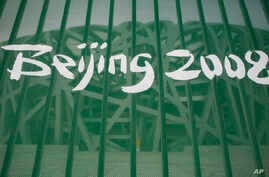 """FILE -  A protective fence shows a Beijing 2008 logo outside the National Stadium, known as the """"Birds Nest,"""" in Beijing, China, Aug. 7, 2008. The IOC says 31 athletes in six sports have tested positive in a re-testing of their doping samples from th"""