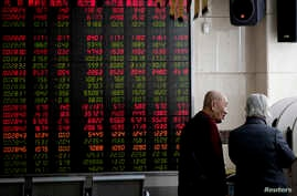 Investors chat near an electronic board displaying stock prices at a brokerage house in Beijing, Jan. 18, 2019. Chinese stocks rose Friday on signs of possible progress in negotiations over Beijing's tariff war with Washington.