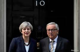 FILE - Britain's Prime Minister Theresa May welcomes Head of the European Commission, President Jean-Claude Juncker to Downing Street in London, April 26, 2017.