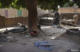 Local resident Issa Dembele stands next to munitions, believed to belong to Islamist rebels, stockpiled in the courtyard of his house in Diabaly, Mali, Jan. 23, 2013.
