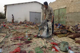 A man holds burnt garments at the site of a suicide bombing in Yemen's southern city of Jaar August 5, 2012.