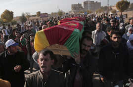 Mourners carry the coffin with the body of a Kurdish fighter, killed in the fighting with the militants of the Islamic State group in Kobani, Syria, during the funeral of three fighters, at the cemetery in Suruc, on the Turkey-Syria border, Thursday,...