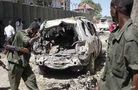 FILE - Security forces inspect the scene of a car bomb attack in the capital Mogadishu, Somalia, April 11, 2016. A car bomb exploded outside a restaurant packed with lunchtime customers, killing at least five people according to witnesses.
