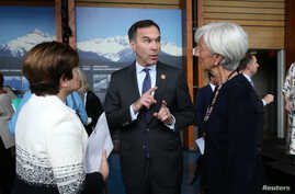 Canada's Minister of Finance Bill Morneau speaks to CEO of the World Bank Kristalina Georgieva and Managing Director of the International Monetary Fund Christine Lagarde, right, as he wears a G-7 Summit pin, in Whistler, British Columbia, Canada, May