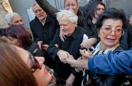 FILE - Fikret Abdic, center, greets his family members upon his release from prison in Pula, Croatia,  March 9, 2012.