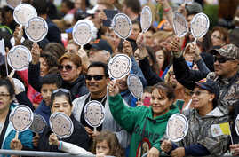 People wave images of Pope Francis as they wait for him to arrive for a Mass at the Cathedral Basilica of Saints Peter and Paul in Philadelphia, Sept. 26, 2015.