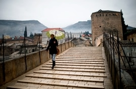 A woman crosses the old bridge in Mostar in Bosnia and Herzegovina, Jan. 20, 2013. The old bridge connects the two sides together and also has a symbolic meaning connecting the two ethnic sides of the city.