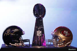 The helmets of the San Francisco 49ers and the Baltimore Ravens sit beside the Vince Lombardi trophy before a press conference ahead of the NFL's Super Bowl XLVII in New Orleans, Louisiana, Feb. 1, 2013.