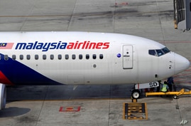 Ground staff take a break under a Malaysia Airlines plane at Kuala Lumpur International Airport in Sepang, Malaysia, March 9, 2014.