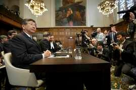 Japanese Ambassador to the Netherlands Koji Tsuruoka, left, waits for the International Court of Justice to deliver its verdict in The Hague, Netherlands, March 31, 2014.