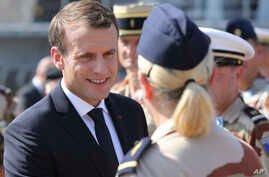 French President Emmanuel Macron shakes hands with French military personnel at the naval base during his second day of visit in Abu Dhabi, United Arab Emirates, Thursday, Nov. 9, 2017.
