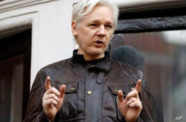 FILE - In this May 19, 2017, WikiLeaks founder Julian Assange gestures to supporters outside the Ecuadorian embassy in London, where he has been in self imposed exile since 2012.