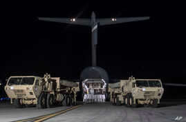 In this photo provided by U.S. Forces Korea, trucks carrying U.S. missile launchers and other equipment needed to set up the Terminal High Altitude Area Defense (THAAD) missile defense system arrive at the Osan air base in Pyeongtaek, South Korea, Ma