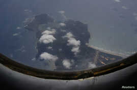A Vietnam Air Force aircraft AN-26 flies over Con Dao island during a mission to find the missing Malaysia Airlines flight MH370, March 12, 2014.