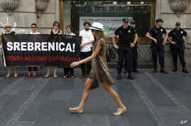 "Serbian police officers guard members of the anti-war organization ""Women in Black"", holding a banner reading: "" Srebrenica! We will never forget"" as part of a protest in Belgrade, Serbia, July 6, 2015."