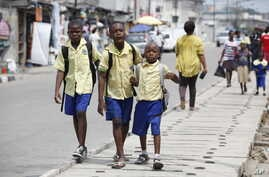 FILE - School children walk in the street in Lagos, Nigeria, June 17, 2014.