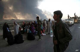 Smoke rises as people flee the clashes between Iraqi security forces and members of the Islamic State group in the area of Mosul, Iraq, Oct. 18, 2016. Amnesty International is asking Iraqi and Kurdish forces not to detain, torture or kill male Sunni