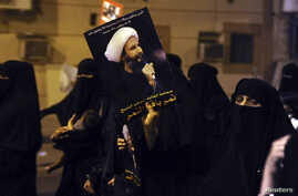 FILE - A protester holds up a picture of Sheikh Nimr al-Nimr during a rally at the coastal town of Qatif.