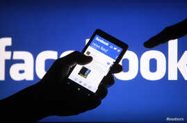 FILE - A smartphone user displays a Facebook newsfeed in a May 2, 2013, photo illustration.