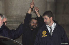 """FILE - Ali Charaf Damache, also known by the alias """"Black Flag,"""" is accompanied by Irish law enforcement officials as he appears at Waterford District Court to be remanded into custody after being arrested on terrorism charges in Waterford, Ireland,"""