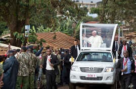 Pope Francis waves to local residents as he drives to St. Joseph The Worker Catholic Church in the Kangemi slum of Nairobi, Kenya Friday, Nov. 27, 2015.