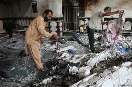 Relatives inspect the damage after an overnight suicide attack at a mosque in Herat, Afghanistan, Aug. 2, 2017.