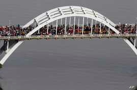 "In this aerial photo, crowds of people move in a symbolic walk across the Edmund Pettus Bridge, Sunday, March 8, 2015, in Selma, Ala. This weekend marks the 50th anniversary of ""Bloody Sunday,' a civil rights march in which protestors were beaten, tr"