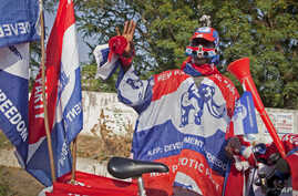 FILE - A supporter of the New Patriotic Party (NPP) wears campaign paraphernalia on the side of a road in Accra, Ghana, Nov. 23, 2012. The NPP has said it will challenge the ruling National Democratic Congress party with its own manifesto October 18.