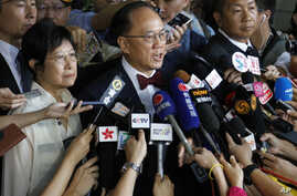 FILE - Donald Tsang, center, former leader of Hong Kong talks to reporters with his wife Selina as they leave a magistrate's court in Hong Kong, Oct. 5, 2015. Tsang faces misconduct charges over a luxury apartment rental in mainland China.