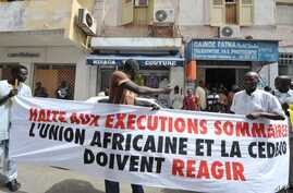 """Protesters gather outside the Gambian Embassy in Senegal on August 30, 2012. The banner reads : """" Stop summary executions. The African Union and ECOWAS must react."""""""