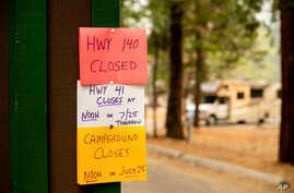 A sign warns departing campers of closures, July 25, 2018, in Yosemite National Park, Calif. Parts of the park closed Wednesday as firefighters work to contain the Ferguson Fire.