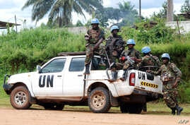 FILE - Blue-helmeted members of the U.N. Organization Stabilization Mission in the Democratic Republic of Congo sit on the back of a pickup truck in Beni, Oct. 23, 2014.