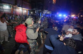 A Lebanese soldier opens fire into the air to disperse people who gathered around a man (on the ground) whom they claimed was a suspected attacker in Burj al-Barajneh, southern Beirut, Lebanon, Thursday, Nov. 12, 2015.