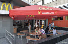 People sit outside a closed McDonald's restaurant in Moscow, August 20, 2014.