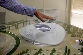 In this photo taken during a government organized media tour, an official makes a point using a scale model of the Al-Wakra Stadium, currently under construction for the 2022 World Cup, in Doha, Qatar, Monday, May 4, 2015. (AP Photo/Maya Alleruzzo)