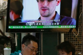 A TV screen shows a news report on Edward Snowden, a former CIA employee who leaked top-secret documents about sweeping U.S. surveillance programs, at a restaurant in Hong Kong, June 12, 2013.